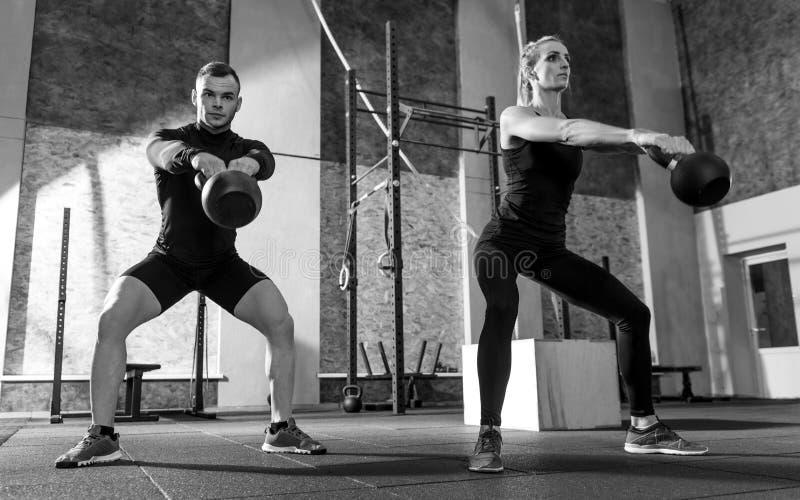 Атлетические партнеры разминки держа kettlebells перед ими стоковые фото