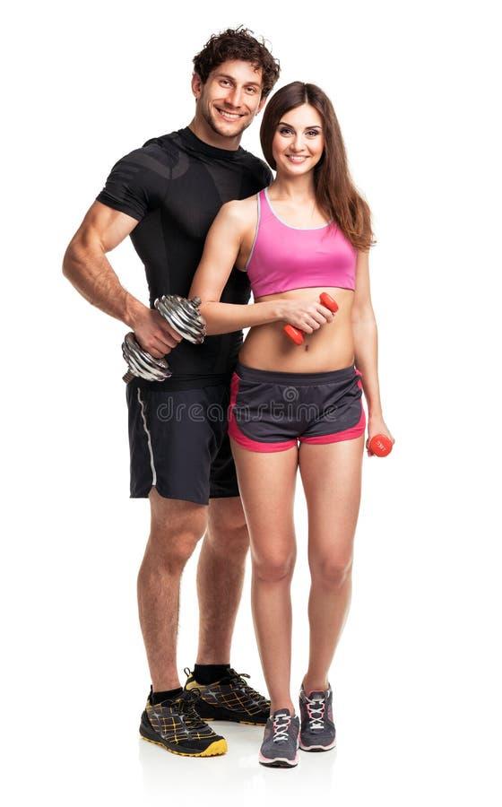 Атлетические пары - человек и женщина с гантелями на белизне стоковая фотография