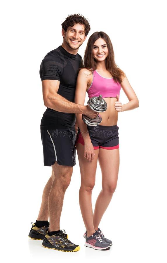 Атлетические пары - человек и женщина с гантелями на белизне стоковая фотография rf