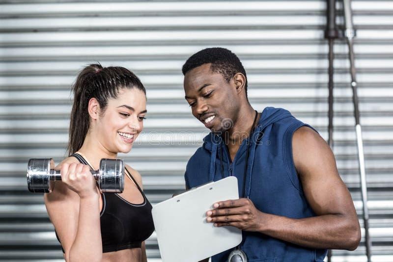 Атлетический тренер объясняя план разминки к женщине стоковая фотография