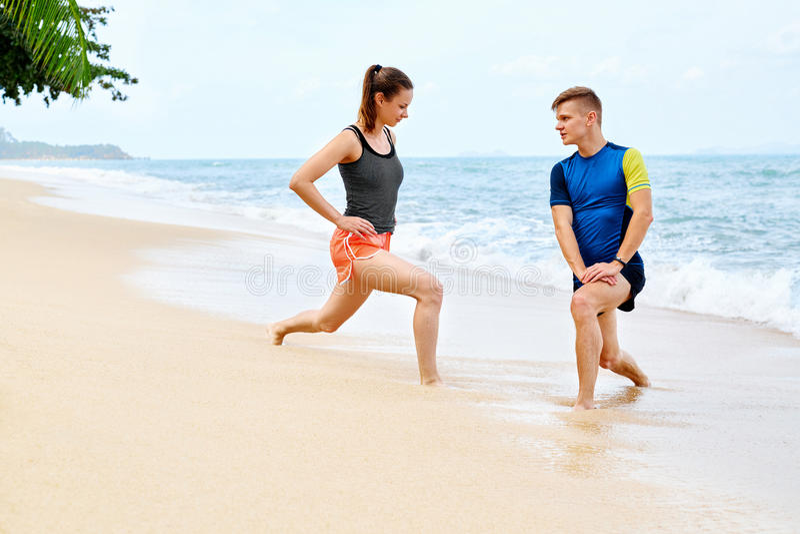 атлетических Подходящий протягивать пар, работая на пляже Спорт, f стоковое изображение rf