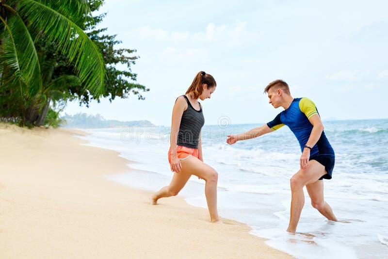 атлетических Подходящий протягивать пар, работая на пляже Спорт, f стоковое фото