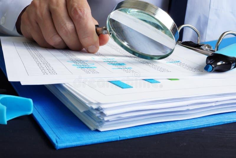Аудитор работает с финансовыми документами Проверка или оценки стоковая фотография rf