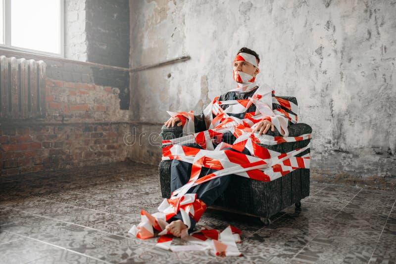 Аутистическое усаживание на стуле в середине комнаты стоковая фотография rf
