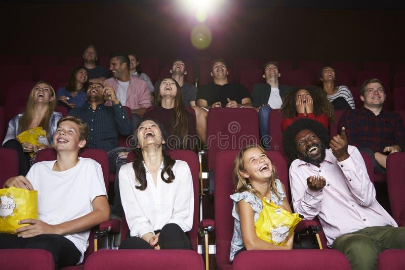 Аудитория в кино смотря фильм комедии стоковое изображение