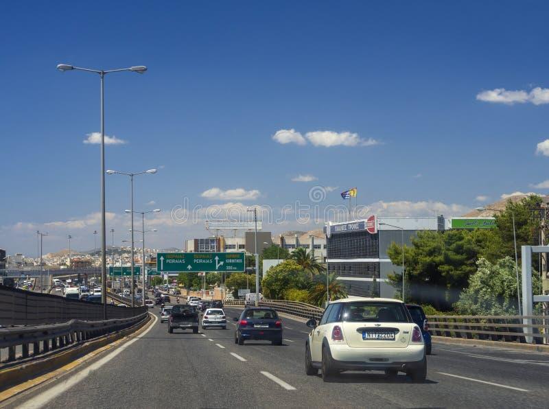 Афина, Греция Июль 2019: Движение на шоссе столицы с указателем поселений, автомобилей и мотоциклов на летний день стоковая фотография
