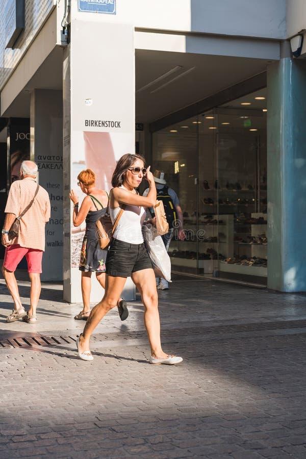 АФИНА, ГРЕЦИЯ - 17-ОЕ СЕНТЯБРЯ 2018: Люди висят вне, идущ через известный блошиный рынок улицы в квадрате Monastiraki стоковое изображение rf