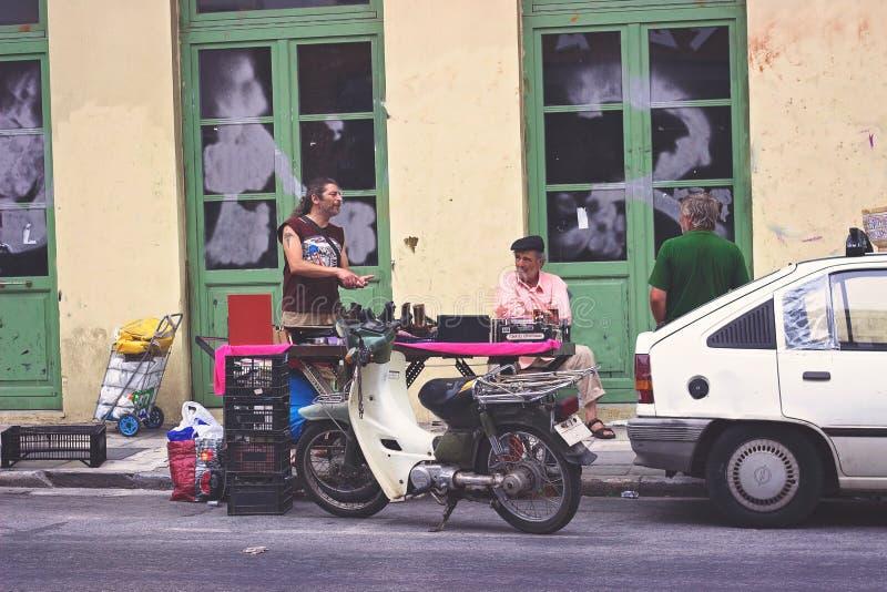 АФИНЫ, ГРЕЦИЯ: Укомплектуйте личным составом торговые сделки на блошинном в улице района Psiri, Monastiraki, Афинах стоковое фото