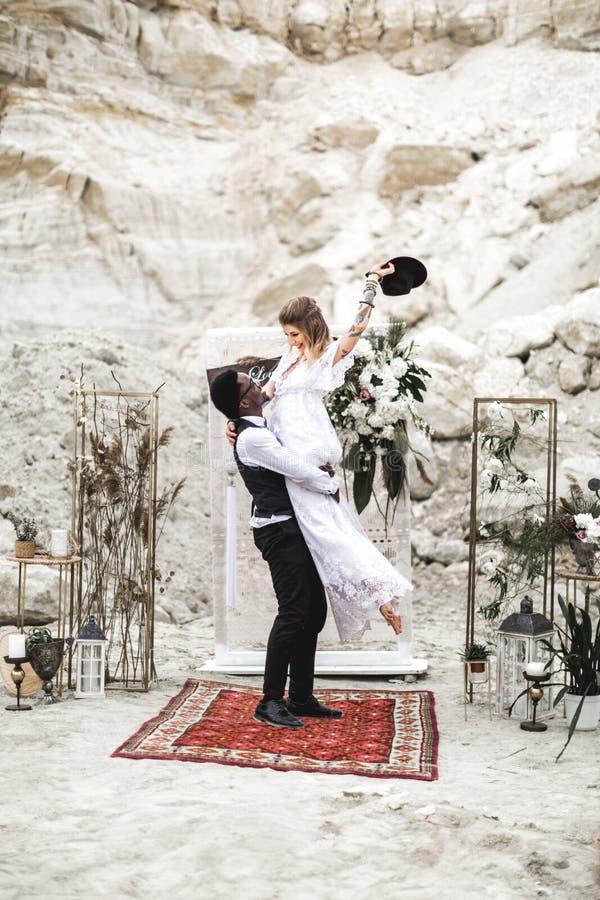 Африканец холит и кавказский один другого обнимать невесты в стиле boho перед сводом свадьбы от свежих цветков groom стоковые фотографии rf