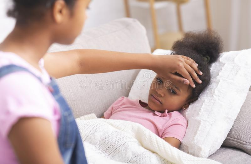 Африканская американка-подросток, трогая лоб своей больной младшей сестры стоковые фото