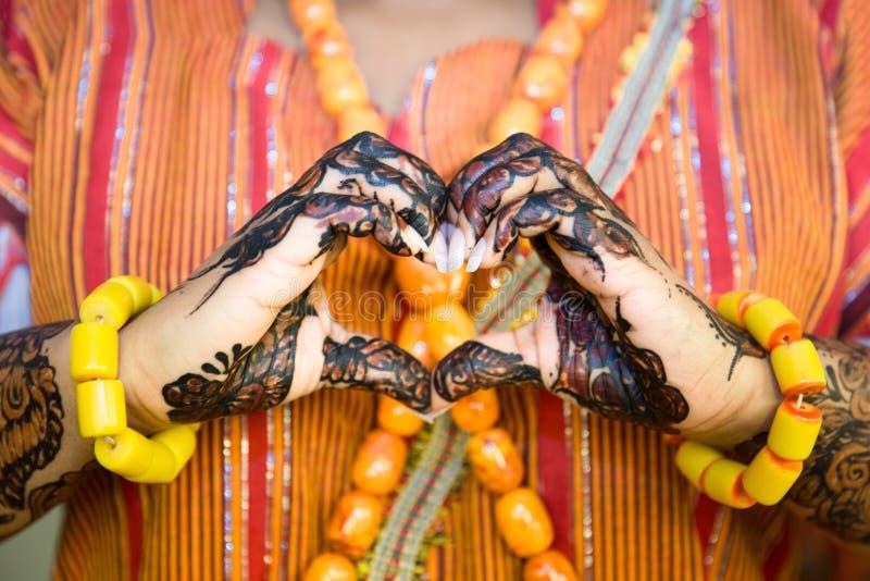 Африканская женщина делая форму сердца с хной покрасила руки стоковые фотографии rf
