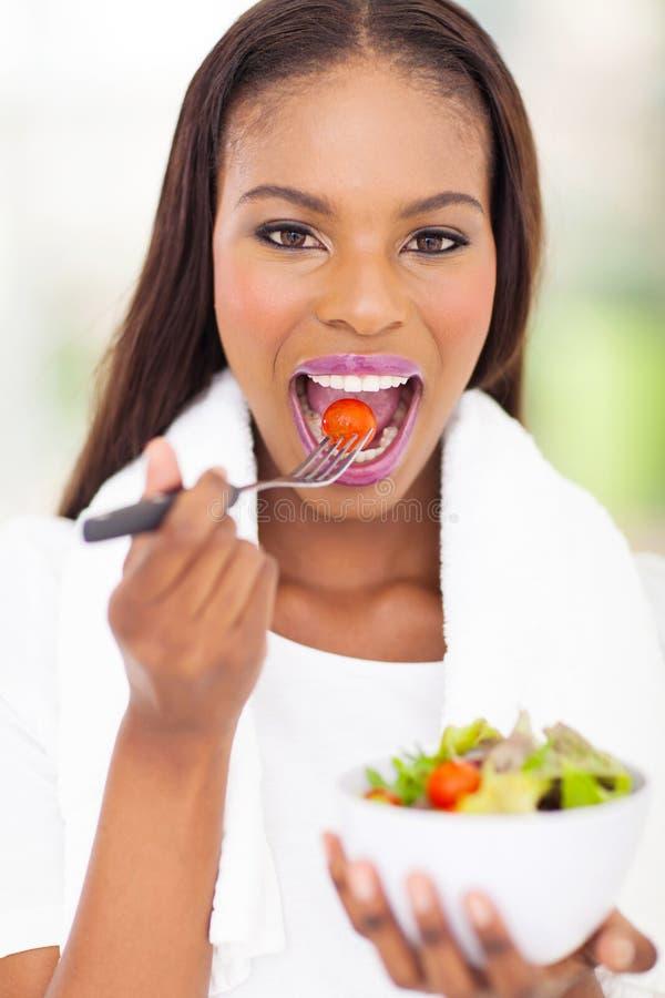 Африканская женщина есть салат стоковые фото