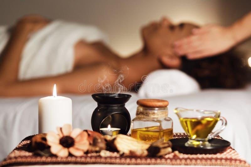 Африканская женщина имея массаж стороны, ослабляя в салоне спа стоковое фото
