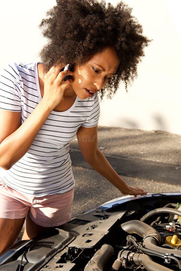 Африканская женщина смотря ее сломленный автомобиль и звоня телефонный звонок для помощи стоковая фотография rf