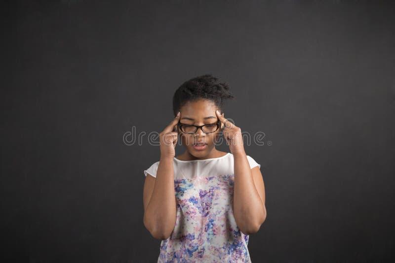 Африканская женщина с пальцами на висках думая на предпосылке классн классного стоковое изображение rf