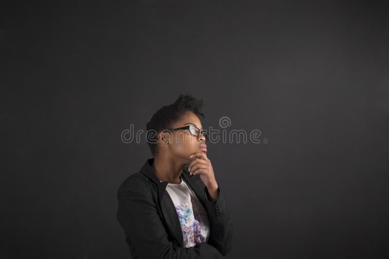 Африканская женщина с рукой на подбородке думая на предпосылке классн классного стоковая фотография rf