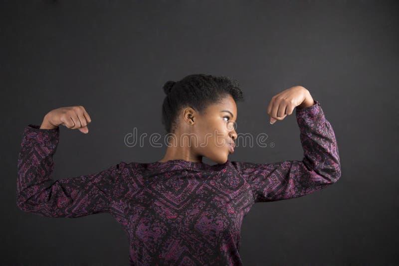 Африканская женщина с сильными оружиями на предпосылке классн классного стоковые изображения