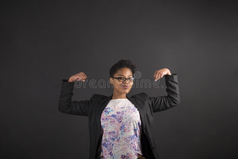 Африканская женщина с сильными оружиями на предпосылке классн классного стоковое фото rf