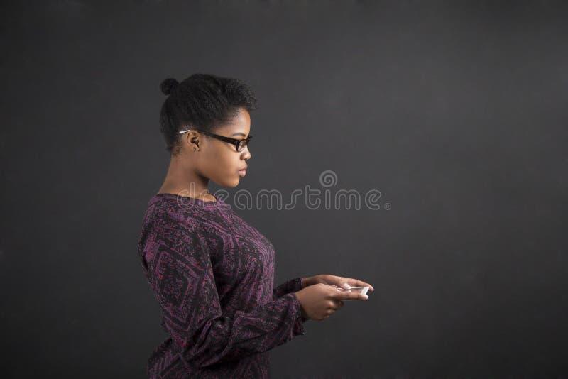 Африканская женщина с таблеткой на предпосылке классн классного стоковые изображения rf