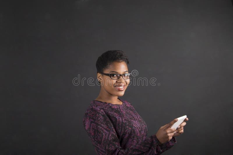 Африканская женщина с таблеткой на предпосылке классн классного стоковое изображение