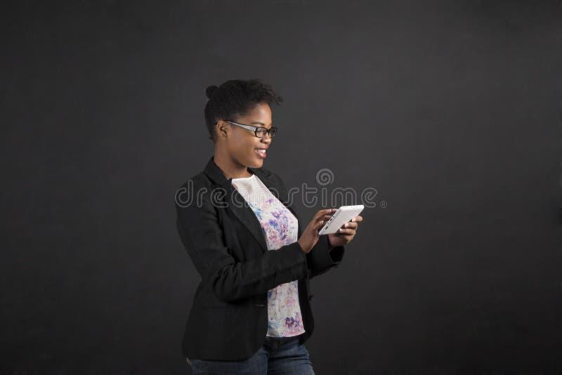 Африканская женщина с таблеткой на предпосылке классн классного стоковые изображения