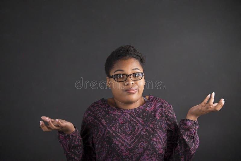 Африканская женщина с я не знаю жест на предпосылке классн классного стоковые фотографии rf