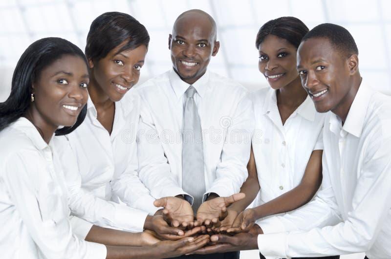 Африканская команда дела представляя с открытыми руками стоковые фотографии rf