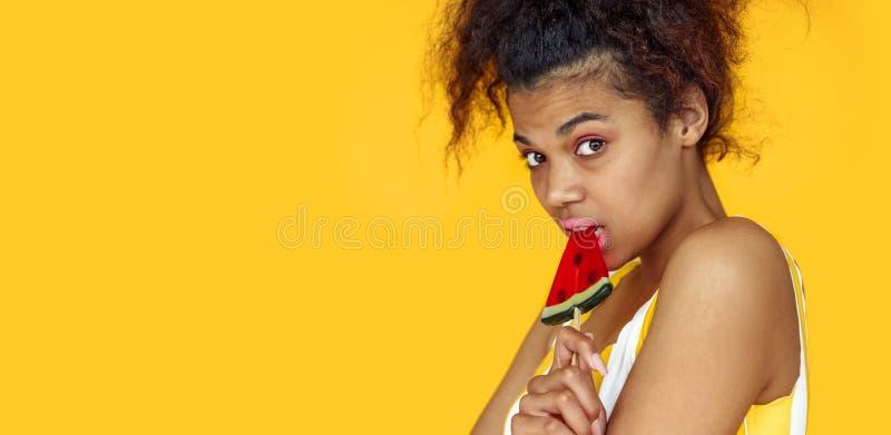 Африканская милая предназначенная для подростков конфета владением девушки на желтой предпосылке студии лета, знамени стоковое фото