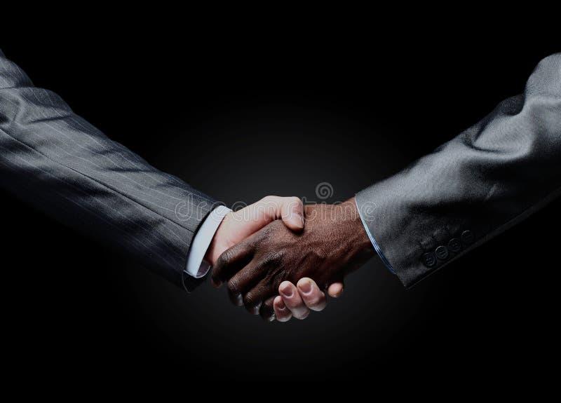 Африканская рука ` s бизнесмена тряся белую руку ` s бизнесмена стоковая фотография
