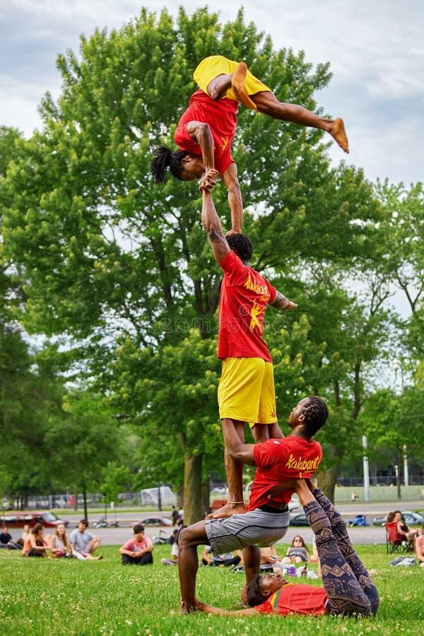 Африканские акробаты выполняя акробатику показывают перед аудиторией в парке держателя королевском, Монреале, Канаде стоковые фото