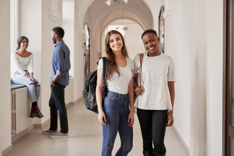 Африканские и кавказские студентки отдыхая на коридоре стоковая фотография rf