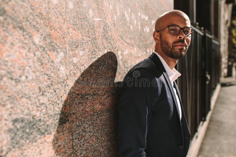 Африканский бизнесмен полагаясь к стене outdoors стоковые фото