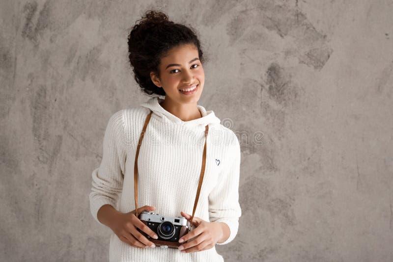 Африканский женский усмехаться фотоснимка, держа камеру над бежевой предпосылкой стоковая фотография