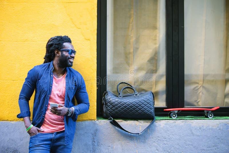Африканский молодой человек используя чернь в улице стоковые изображения