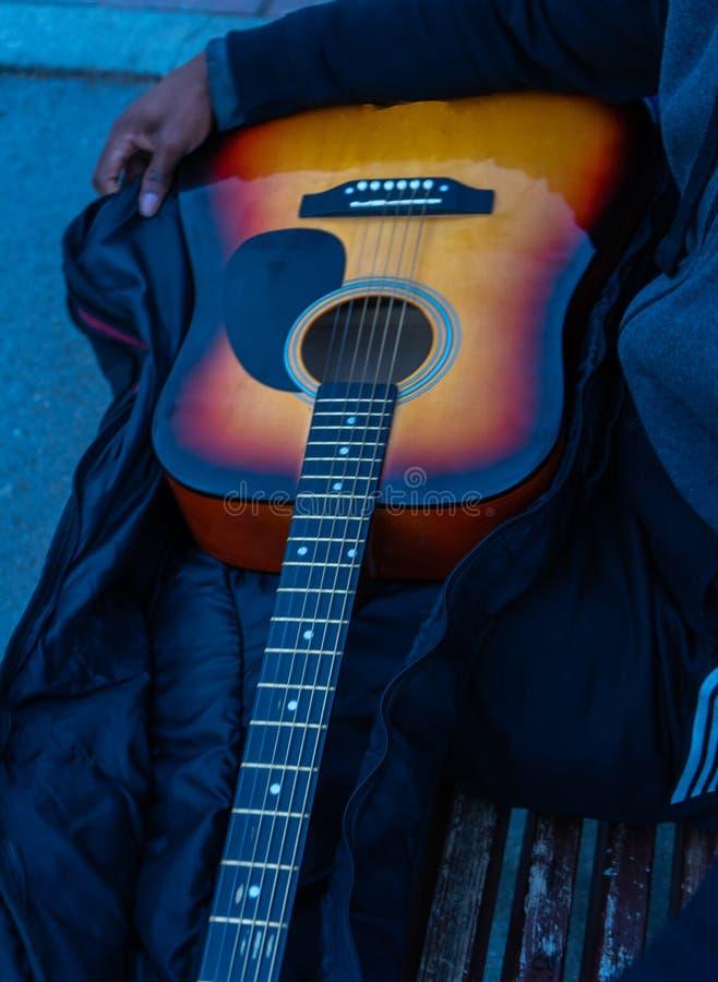Африканский парень с акустической гитарой в чемодане получая готовый сыграть в парке стоковые изображения rf