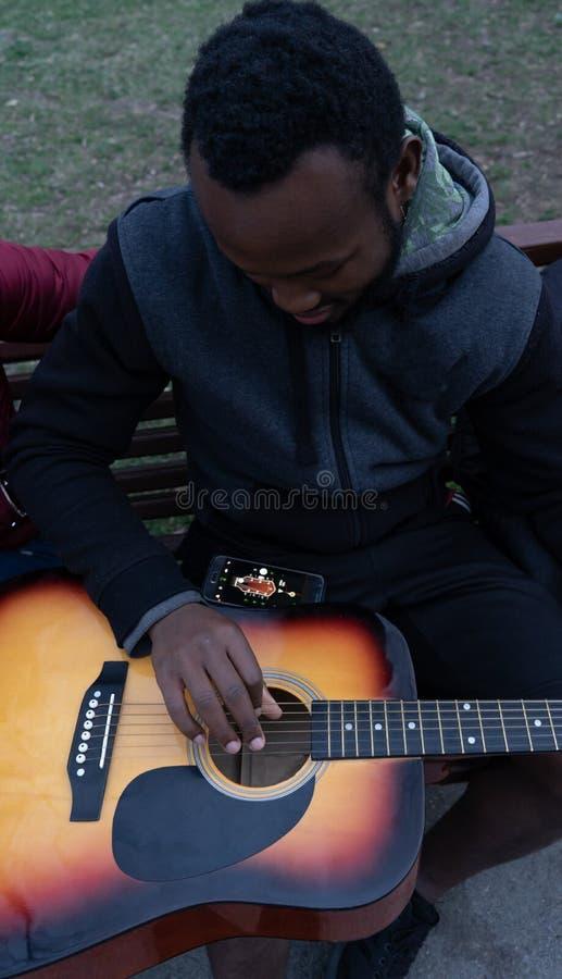 Африканский парень с акустической гитарой в чемодане получая готовый сыграть в парке стоковые фотографии rf