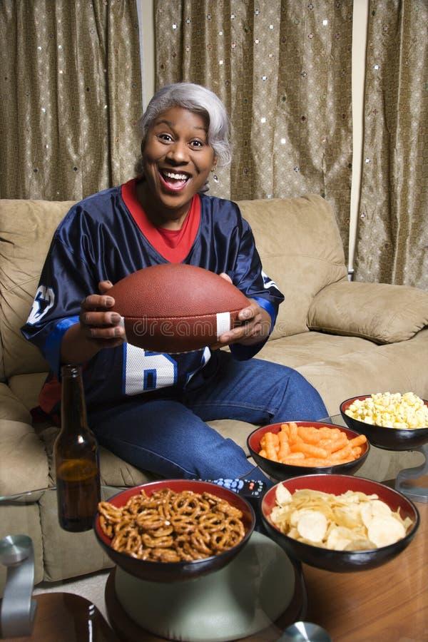 африканский постаретый американский футбол держа среднюю женщину стоковая фотография
