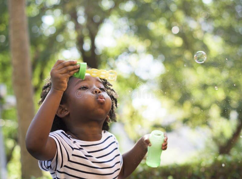 Африканский ребенк играя с пузырями стоковые фотографии rf