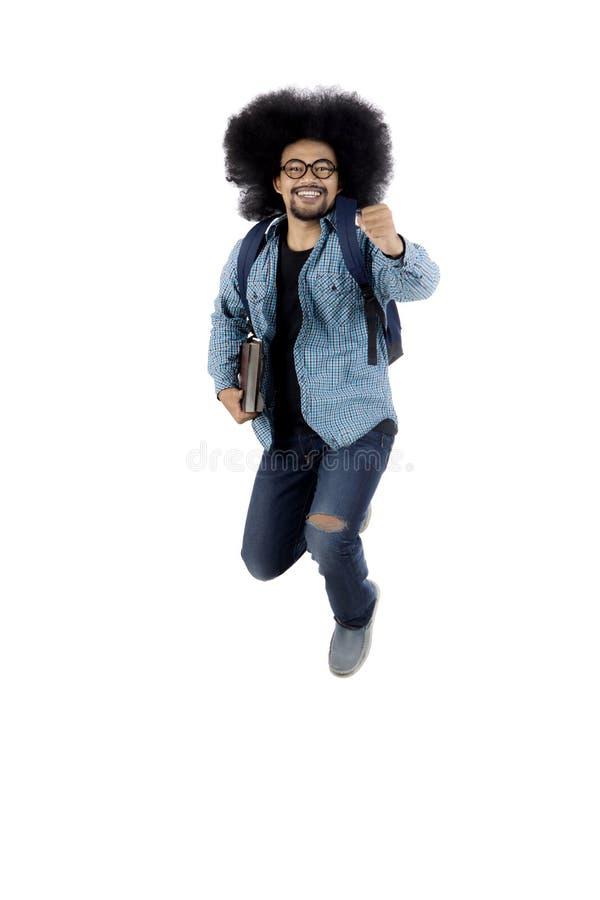 Африканский студент скача в студию стоковое изображение rf