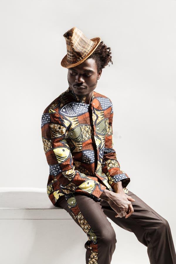 Африканский человек в национальном костюме kongo сидит на coub стоковое фото rf