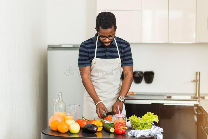 Африканский человек подготавливая здоровую еду дома в кухне стоковое изображение