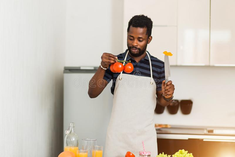 Африканский человек подготавливая здоровую еду дома в кухне стоковое фото rf