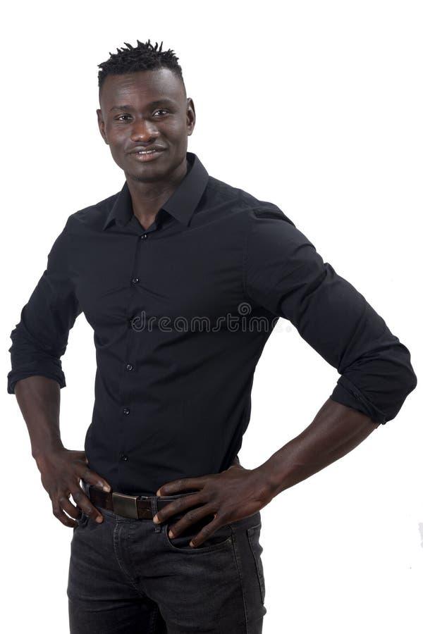 Африканский человек усмехаясь с оружиями на талии смотря камеру стоковое фото rf