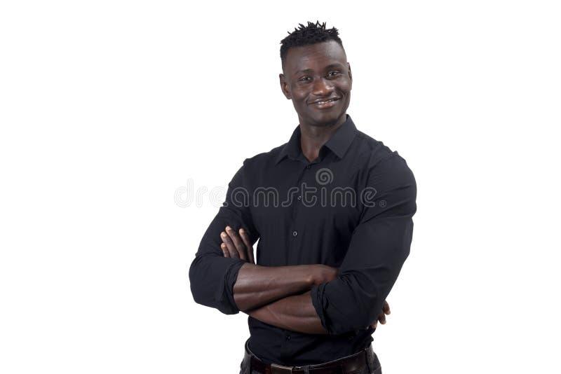 Африканский человек усмехаясь с оружиями пересек смотреть камеру стоковое изображение rf