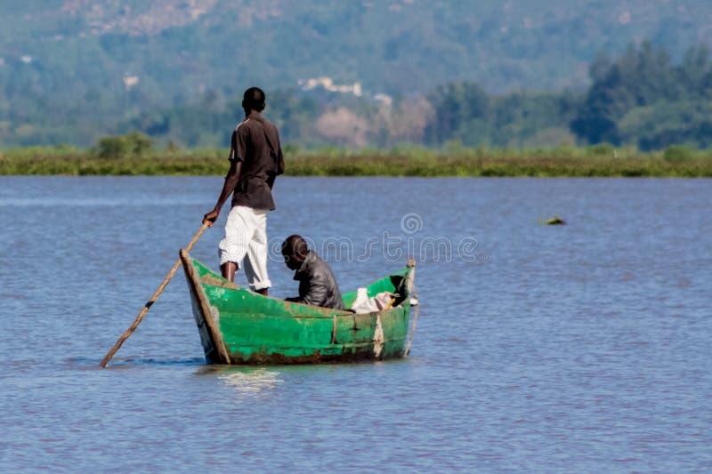 Африканский человек fisher на озере в шлюпке стоковое изображение