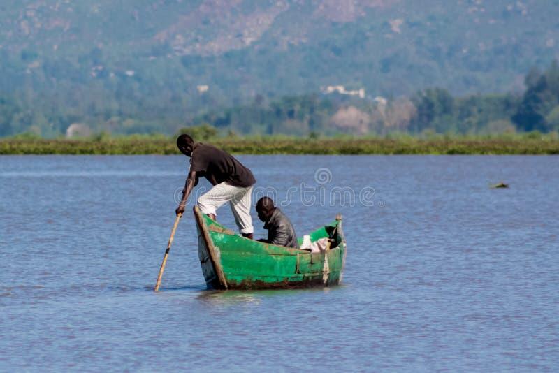 Африканский человек fisher на озере в шлюпке стоковая фотография