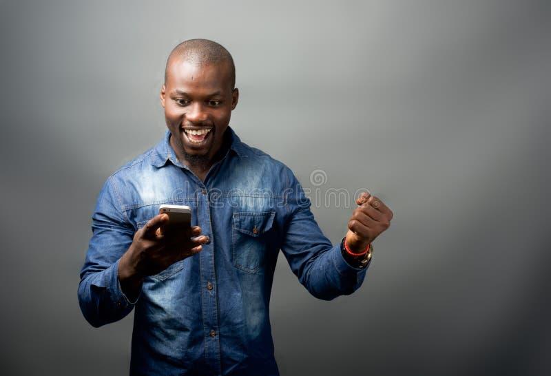 Африканский человек возбужденный на мобильном телефоне стоковая фотография rf