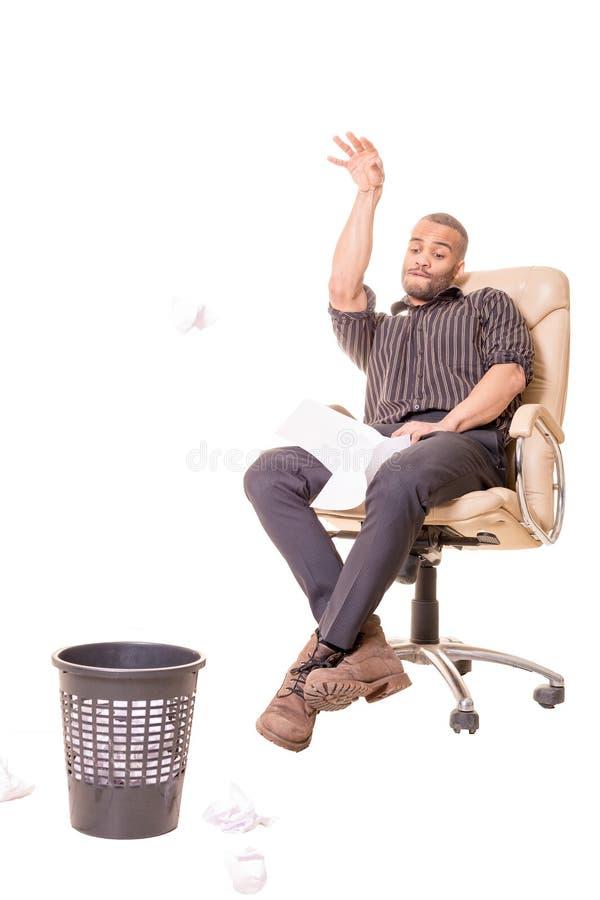 Африканский человек сидя в стуле и играя баскетбол с хламом стоковая фотография