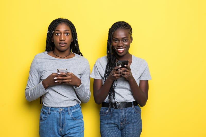 2 африканских молодой женщины выражая ободрение или сюрприз пока оба используя сотовые телефоны изолированные над желтой предпосы стоковые изображения