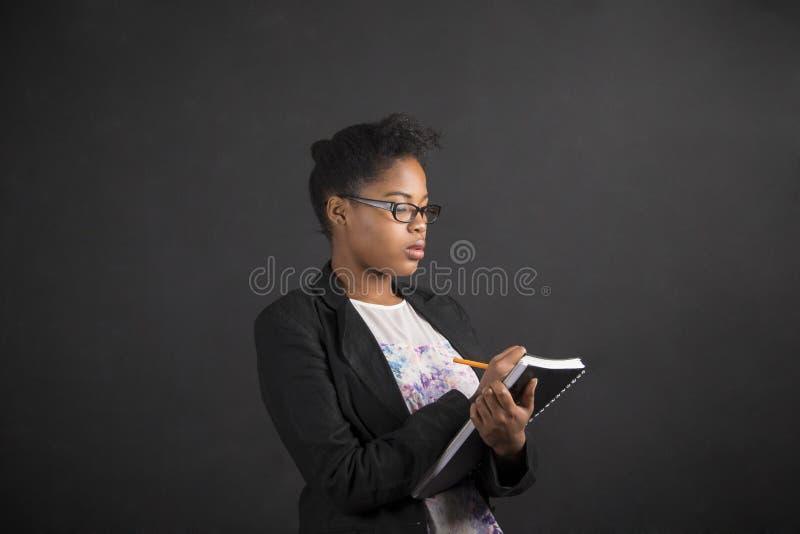 Африканское сочинительство женщины в дневнике книги на предпосылке классн классного стоковое фото